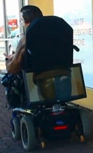 A wheelchair driving along with a computer monitor mounted on the back of the wheelchair showing a video of a bum in jeans