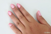 A picture of a left hand with pink nail polish.