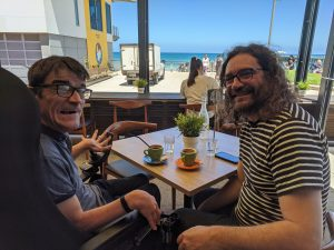 Darryl and Ferg having a coffee at the beach